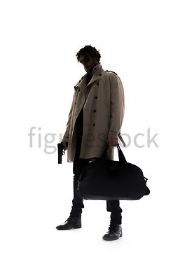 A Figurestock image of a man in a mac, standing, holding a black bag and a gun, in silhouette – shot from low level.