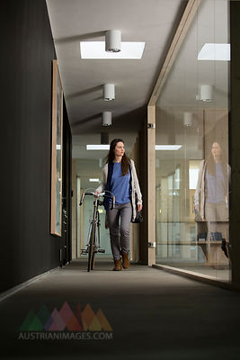 Business woman arriving at office with racing cycle