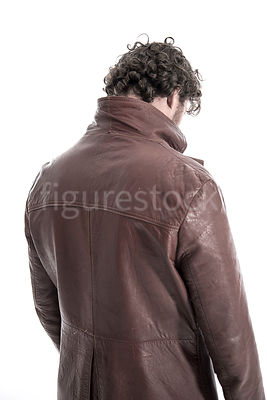 A mystery man in a leather jacket, looking down – shot from eye level.