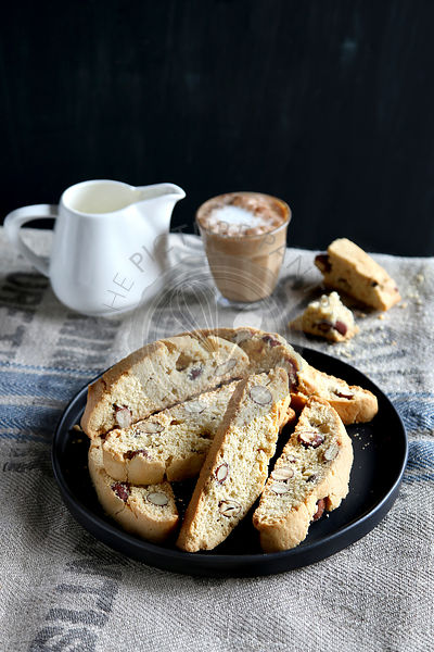 Almond Italian biscotti on a plate with a glass of coffee and a jug of milk in background