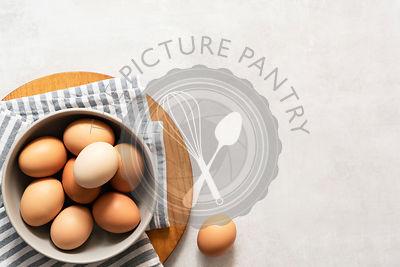 Fresh hen eggs in a bowl on a textured grey background with copyspace.