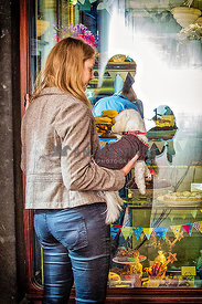 young lady and her dog look in cake shop window