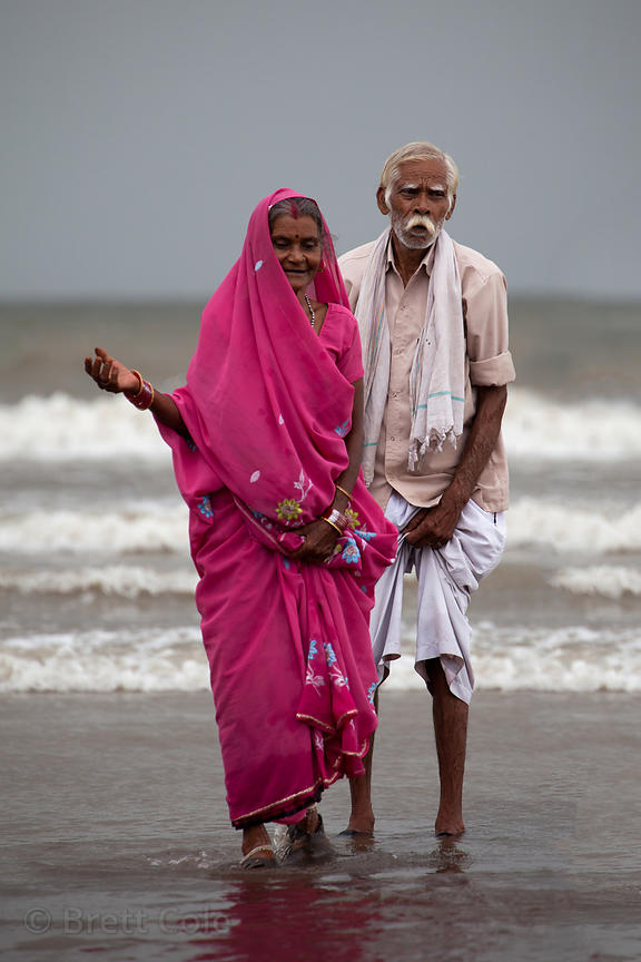 An elderly married couple stands on Juhu beach in Mumbai, India