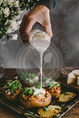 Man's hand pouring sour cream on baked stuffed potatoes with cheese, vegetables and rucola on wooden table. Rustic background...