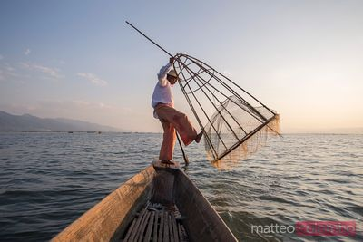 Fisherman with basket fishing from boat, Inle lake, Myanmar (Burma)