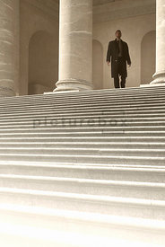 An atmospheric image of a mystery man standing at the top of some steps at a court house.