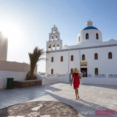Woman in red walking in the whote town of Oia, Santorini, Greece