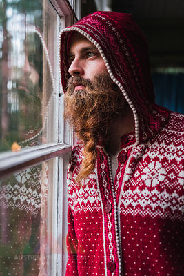Portrait of pensive man with beard wearing hooded jacket looking out of window