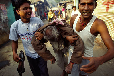 India - New Delhi - Two sons carry their father home who is drunk