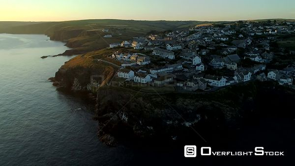 Drone pulls back from the clifftop houses of Port Isaac in Cornwall as the sun rises out of frame.