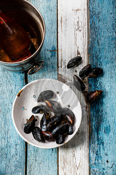 Raw Mussels Clams in vintage ceramic colander and Rose Wine in ice bucket on blue wooden background