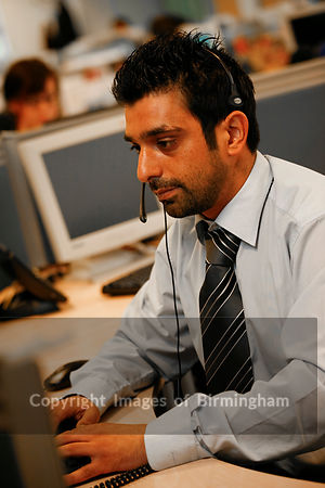 Call centre operator, using a headset to answer the telephone. Service centre.