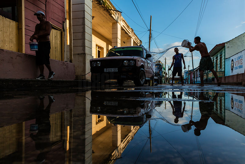 Young Men Washing a Car in the Street in Baracoa