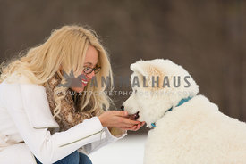 owner with white dog in snow