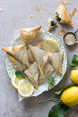 Spanakopita triangles or spinach pie is a Greek savoury pastry. Ingredients include spinach, feta cheese, onions and eggs.