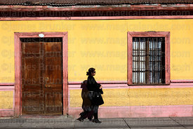Woman walking past typical painted house in Copiapó, Region III, Chile