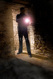 A mystery man with a gun and a torch at the bottom of some cellar steps.