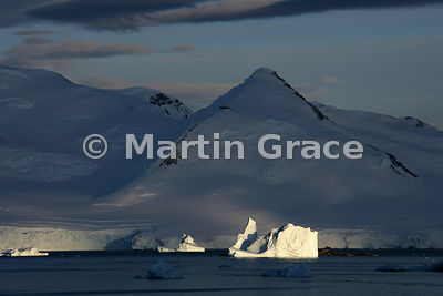 Sunlit land and icebergs in Marguerite Bay, West Graham Land, Antarctica with angled sunlight and blue sky