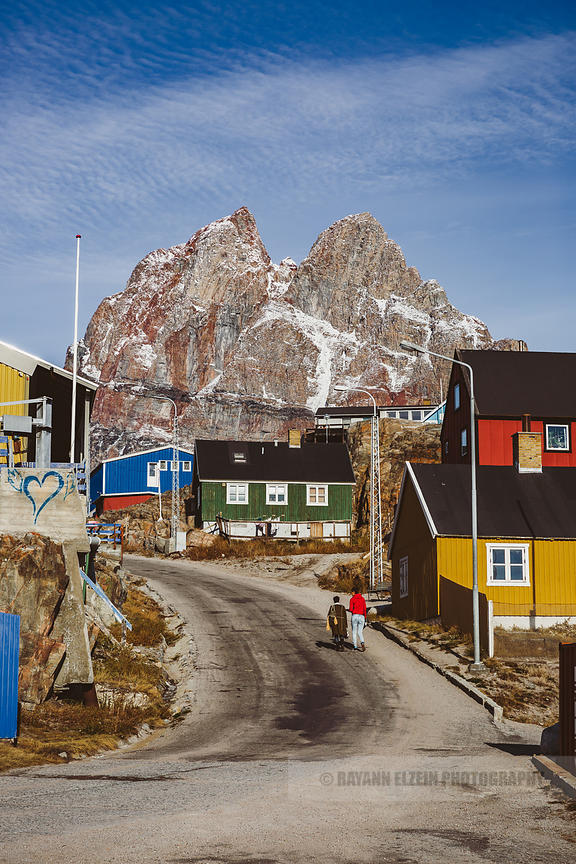 2 women walk up a street in Uummannaq in Greenland