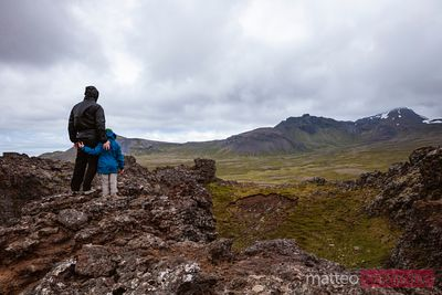 Man and child looking at volcano crater, Snaefellsnes, Iceland