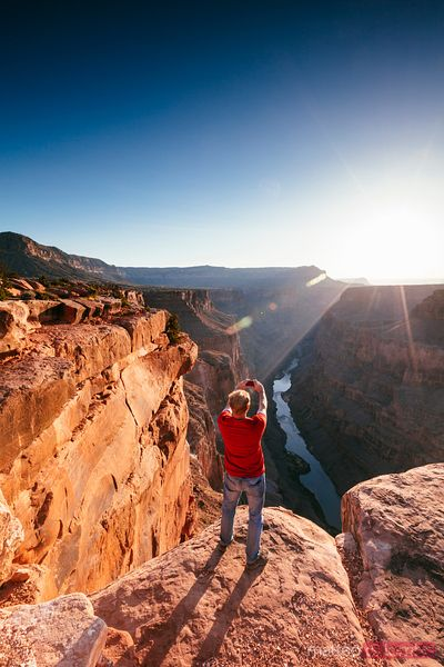 Man taking photo of Grand Canyon at sunrise
