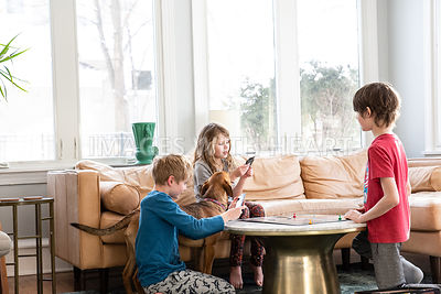 Kids Playing Board Game with Brown Dog