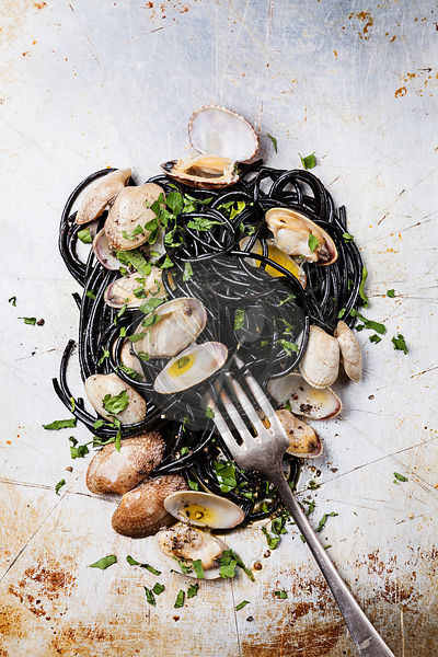 Seafood pasta with clams Spaghetti Vongole on steel textured background