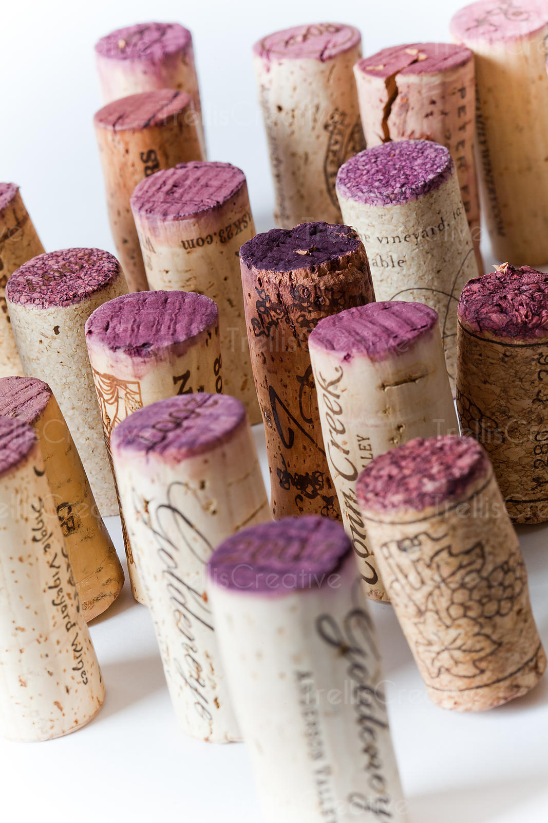 Many used wine stained corks standing on end on white background