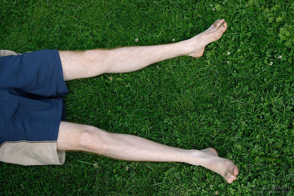 Man´s legs lying on grass
