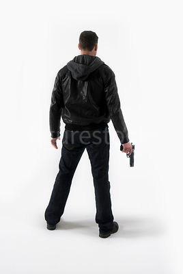A man standing with a gun, from behind – shot from eye level.