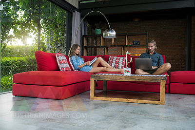 Couple with laptop and book relaxing on red couch in modern living room with glass facade