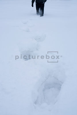 An atmospheric image of a mystery man trudging through deep snow.