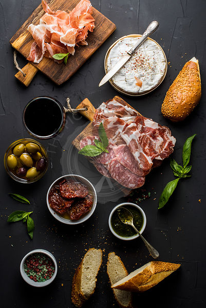 Wine snack set with empty wooden board in center. Glass of red, meat selection, mediterranean olives, sun-dried tomatoes, bag...