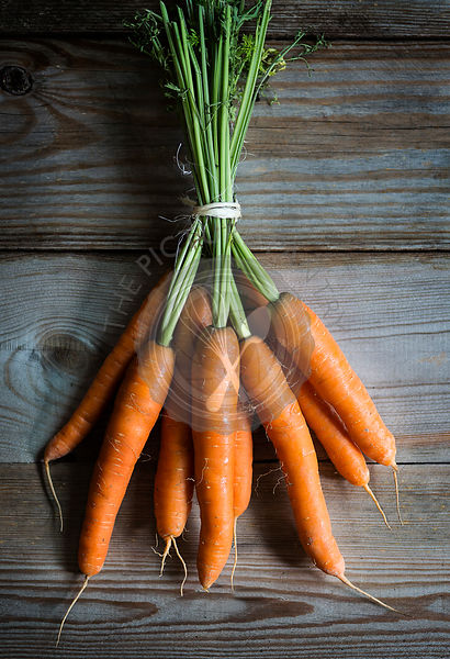 Bunch of fresh carrot on wooden table. Top view