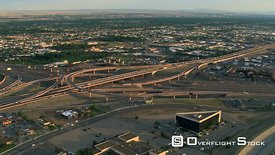 Orbiting Albuquerque freeway interchanges with wide view of plains beyond.