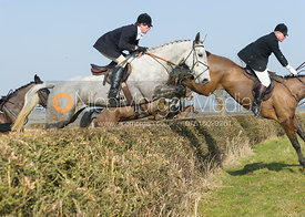 Followers jumping a hedge near Chadwell
