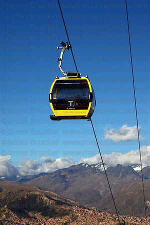 Yellow Line cable car gondolas above La Paz suburbs, Cordillera Real mountains in background , Bolivia