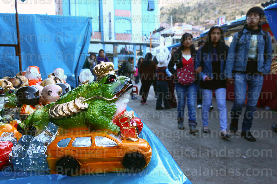 People walking past Chinese Jin Chan money toad and miniature car on market stall for Alasitas festival, Puno, Peru