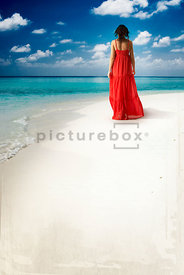 An atmospheric image of a woman in a red dress walking along a tropical beach.