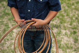 Young cowboy holding a lasso at a rodeo