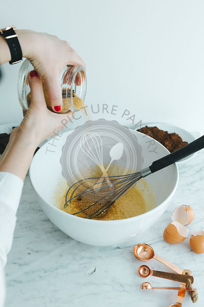 Girl pouring sugar in the bowl with eggs