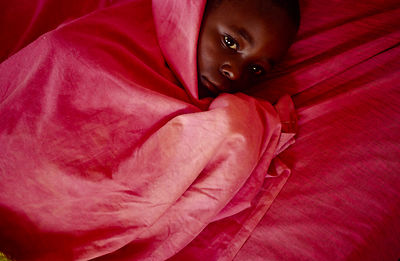 Burundi - Ruyigi - Jean, an orphan of Burundi's ethnic conflict at Shalom House shivers under a blanket with malaria.