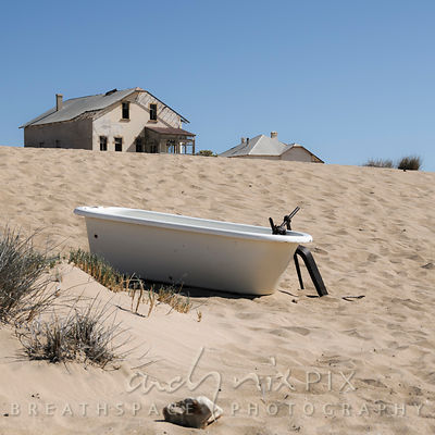 A Victorian bathtup outdoors on a sand dune in the desert, old abandoned and delapidated houses in the background