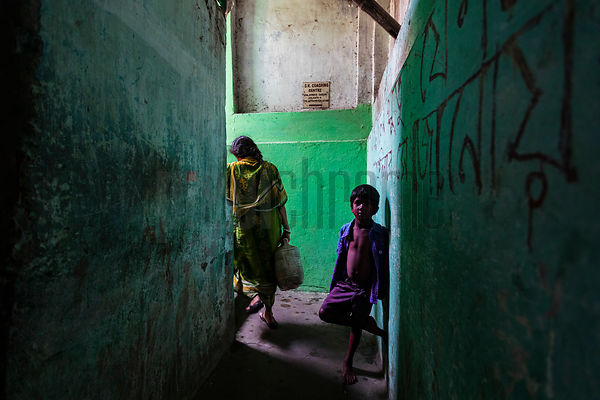 A Young Boy Stained with Holi Color Stands in a Passageway