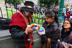A yatiri or shaman uses an Andean hairy armadillo (Chaetophractus nationi) to bless a client, Alasitas festival, La Paz, Bolivia