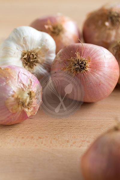 group of pink toned figuera Spanish onions and garlic on light wood table,