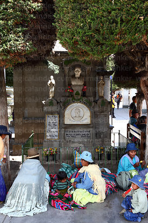 Aymara women and children sitting next to tomb in cemetery during Todos Santos festival, La Paz, Bolivia
