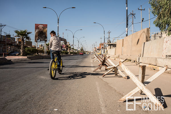 A boy cycles through the near deserted Kurdish quarter of Kirkuk, past a poster of Barzani that has been burned during the co...