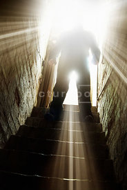 An atmospheric image of the silhouette of a mystery man standing at the top of some cellar steps.
