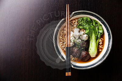 Miso Ramen Asian noodles with shiitake, tofu and pak choi cabbage in bowl on black table background